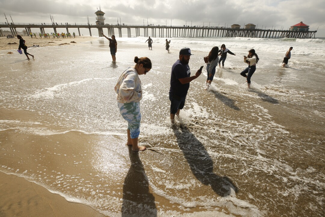 A family wade into shallow water at the beach