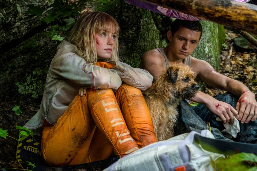 "Daisy Ridley and Tom Holland with a dog in the movie ""Chaos Walking."""
