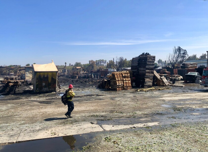 A firefighter checks the vicinity of Atlas Wood Products and Moreno Pallets