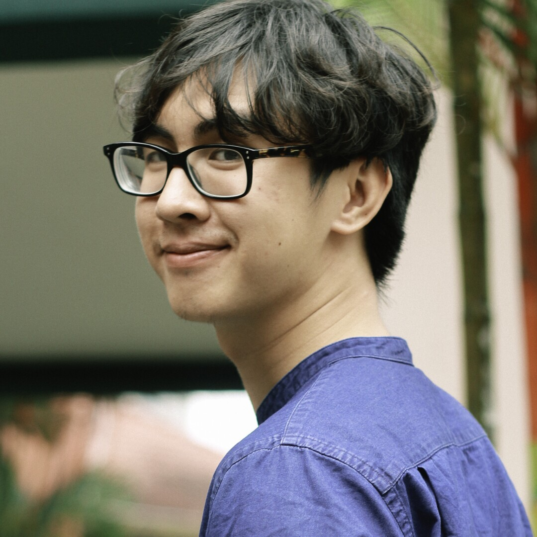 A smiling young man with glasses and tousled dark hair.