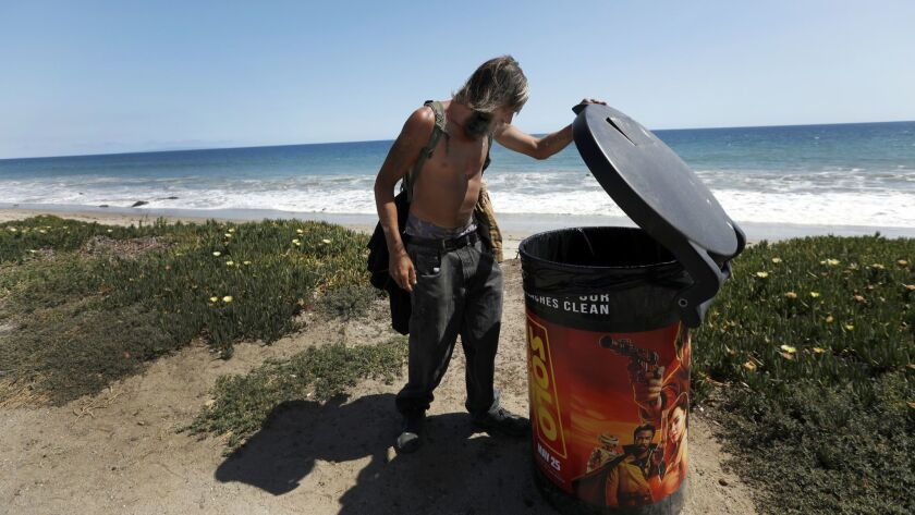 MALIBU, CA MAY 15, 2018: Jack Brown, 37, looks through trashcans on the beach in Malibu, CA May 1