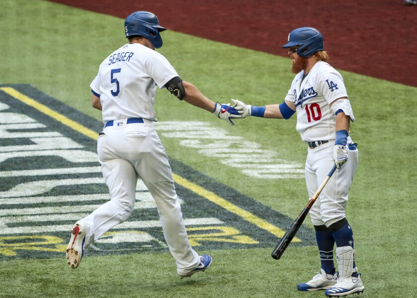 Dodgers shortstop Corey Seager is congratulated by Justin Turner after Seager's first-inning home run in Game 6 of the NLCS.