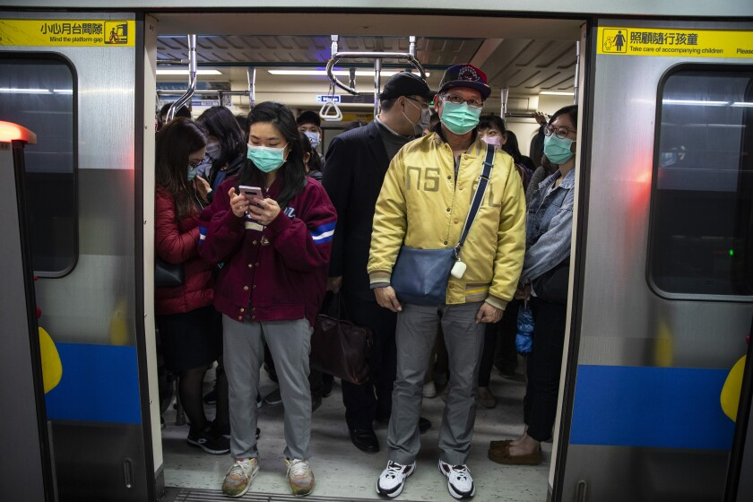Commuters wearing masks pack a subway train in Taipei, Taiwan