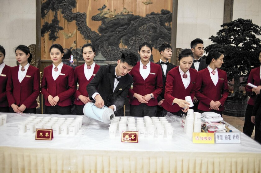 A waiter pours hot water at the opening session of the Chinese People's Political Consultative Conference at the Great Hall of the People in Beijing on March 3, 2016.