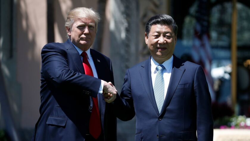 President Donald Trump and Chinese President Xi Jinping shake hands after a bilateral meeting at Mar