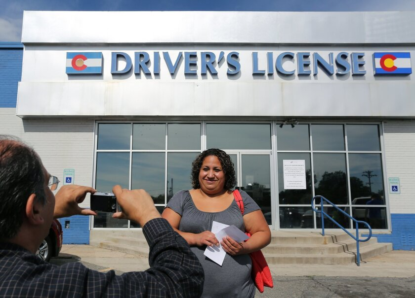 Immigrant and longtime resident in the United States Rosalva Mireles is photographed by Jesus Sanchez of Spanish language newspaper El Commercio, after Mireles was processed for her permanent driver's license, and received a temporary license, at a Department of Motor Vehicles office, in Denver, Fr