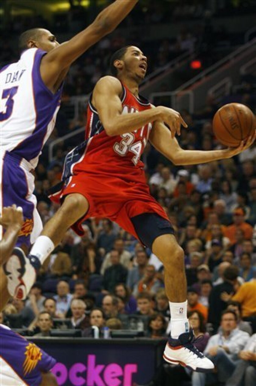 New Jersey Nets guard Devin Harris, right, drives past Phoenix Suns' Boris Diaw of France, during the second quarter of an NBA basketball game on Sunday, Nov. 30, 2008, in Phoenix. (AP Photo/Rick Scuteri)