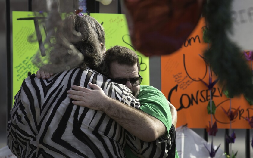 Inland Regional Center client Johnathan Rose, 20, hugs his mother, Marianne Rose, at a makeshift memorial to shooting victims in San Bernardino. The massacre has reopened debate on whether the answer to such shootings is to arm more guards and citizens.