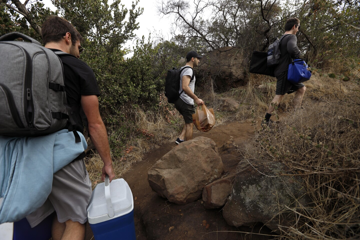 PACIFIC PALISADES, CA - NOVEMBER 30, 2019 - Jack Petros, 28, from left, Dylan Skolnik, 24, and David Weber, 27, members of the Summit Sippers, hike along the Liones Trail in Pacific Palisades on November 30, 2019. Summit Sippers set up impromptu little bars at random view spots on L.A. hiking trails. They wear bow ties, suspenders and one wears a top hat. They are all avid hikers who enjoy the experience of hiking and than setting up their impromptu watering hole. The drinks are free and they won't even take tips. They are careful not to leave trash behind or block spots where hikers might like to take photos. They try and find picturesque sites along LA's hiking trails. (Genaro Molina / Los Angeles Times)