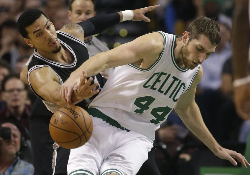 San Antonio Spurs guard Danny Green, left, and Boston Celtics center Tyler Zeller, right, vie for control of the ball in the first quarter of an NBA basketball game, Sunday, Nov. 1, 2015, in Boston. (AP Photo/Steven Senne)