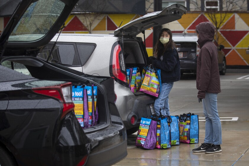 Volunteers Dylan Kim, left, and her mother Soo Kim load a car while helping deliver food to home-bound seniors in Hollywood on Thursday.