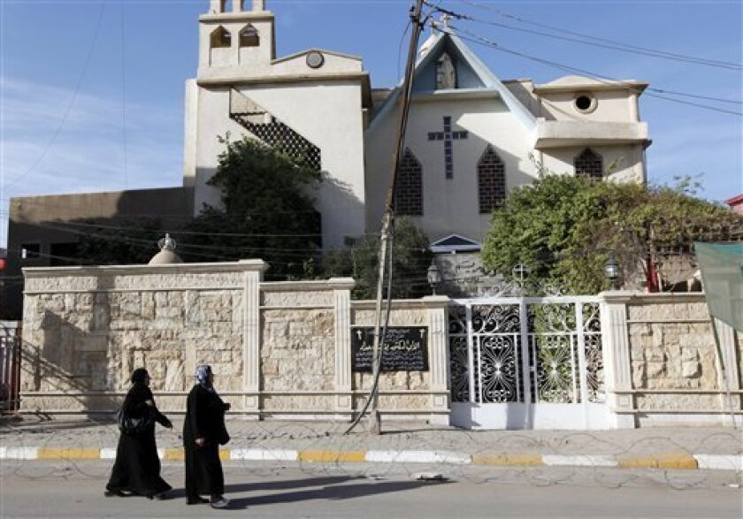 Iraqi women pass by a closed church in Baghdad, Iraq, Wednesday, Dec. 22, 2010. Church officials in Iraq say they have canceled some Christmas festivities in two northern cities over fears of insurgent attacks. (AP Photo/Hadi Mizban)