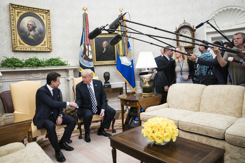 President Donald Trump shakes hands with Italian Prime Minister Giuseppe Conte during a meeting in the Oval Office at the White House on July 30, 2018.
