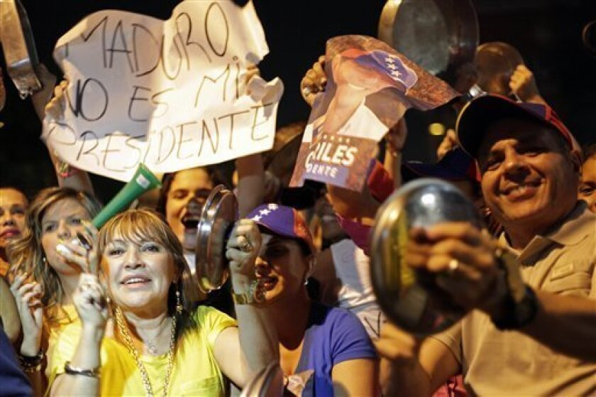Opposition supporters bang pots against President-elect Nicolas Maduro as they protest the presidential election results in Caracas, Venezuela, Thursday, April 18, 2013. Opposition protesters have been protesting the election results every night with pot banging since the Sunday election. Maduro is to be sworn in Friday in the National Assembly at a ceremony being boycotted by the opposition because its deputies are not being allowed to address the body unless they recognize his presidency as le