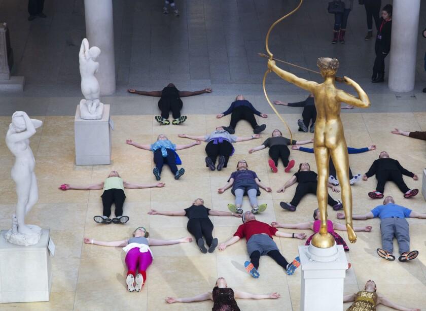 En esta foto del 10 de febrero de 2017, un grupo realiza ejercicios al pie de una escultura de bronce de Diana Cazadora en el Museo Metropolitano de Nueva York. (AP Foto/Mark Lennihan)