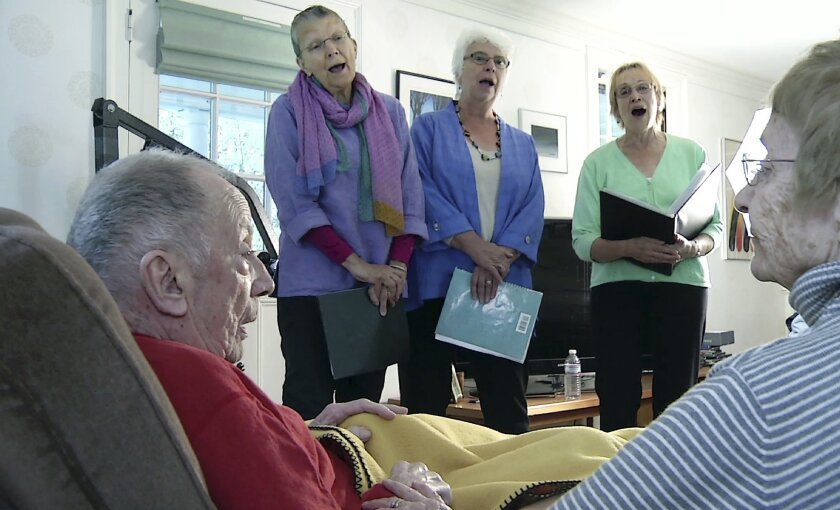 In this May 2, 2016 still image from video, members of JourneySongs choir sing for Norman Doelling, left, and his wife Jean at their home in Newton, Mass. One of a growing number of hospice choirs across the country, the all-volunteer group sings, by invitation only, at the bedsides of the elderly and terminally ill in hospitals, nursing homes and private residences. (AP Photo/Rodrique Ngowi)