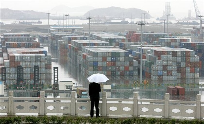 In this file image taken April 6, 2006, a man looks at rows of containers at the Yangshan deep water port off the coast of Shanghai, China. China's exports fell in December for a second month as a trade slump that has prompted a wave of factory closures and layoffs worsened, according to data repo