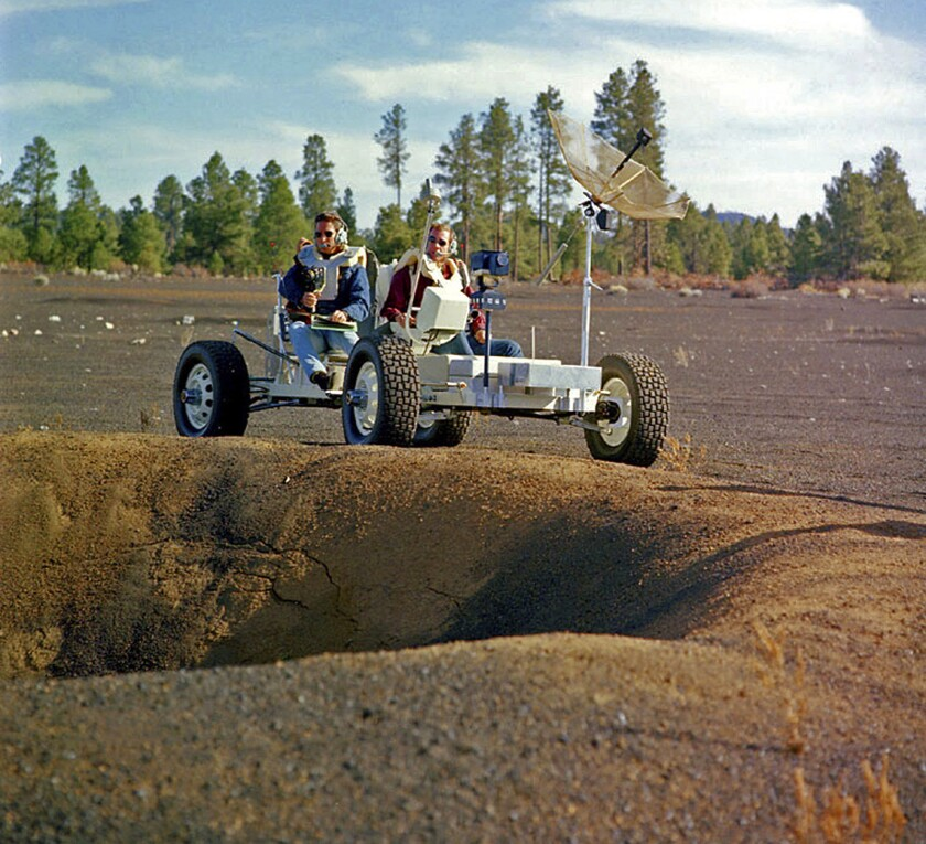 Apollo 15 astronauts Jim Irwin, left, and David Scott drive a prototype of a lunar rover in a volcanic cinder field east of Flagstaff, Ariz. Geology lessons were an important part of the Apollo astronauts' training.