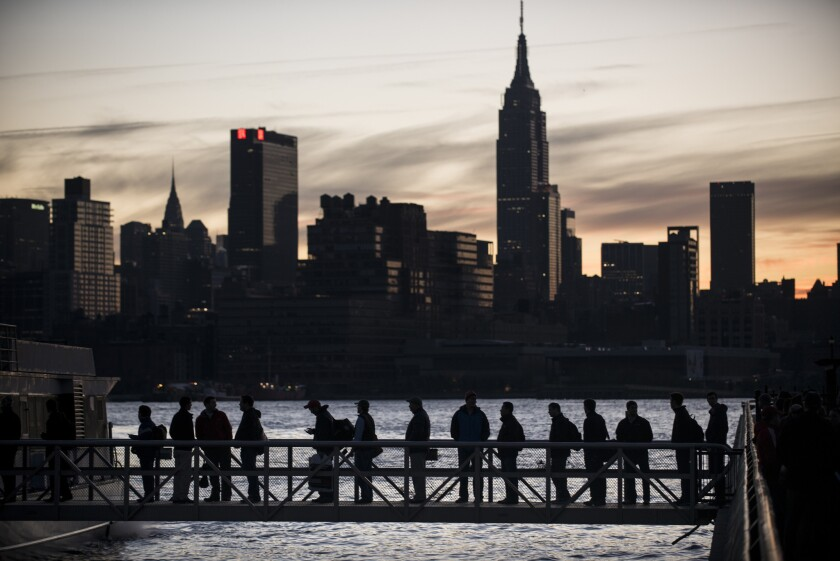 People board a ferry with the Manhattan skyline in the background.