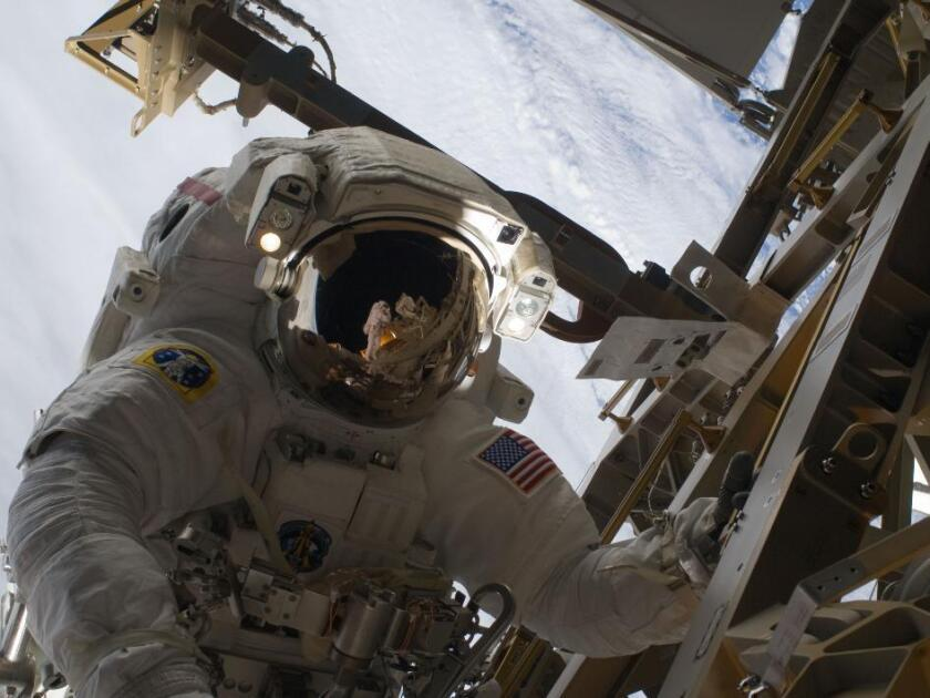 European Space Agency astronaut Christer Fuglesang is visible in the reflection of NASA astronaut Danny Olivas' helmet visor during the STS-128 mission's third spacewalk. NASA, which plans to send astronauts to an asteroid or to Mars in the next few decades, requested a report from the Institute of Medicine that would help lay out an ethics framework for weighing such missions with high potential health risk. The report was released Wednesday.