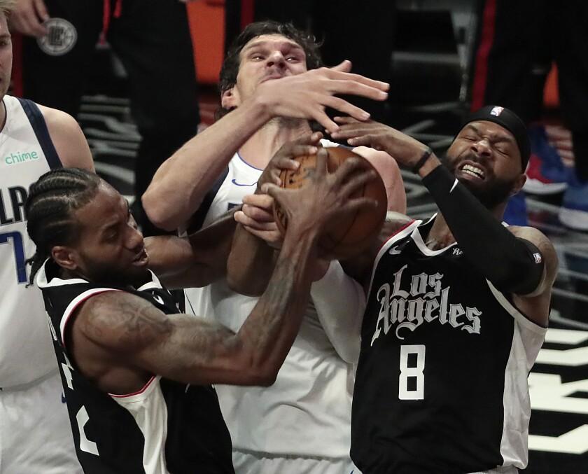 Clippers forwards Marcus Morris Sr. and Kawhi Leonard wrestle the ball from Dallas Mavericks center Boban Marjanovic.