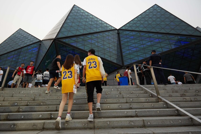 Fans wearing LeBron James shirts arrive to watch a pre-season game between the Lakers and Brooklyn Nets in Shenzhen, in China's southern Guangdong province on Saturday.