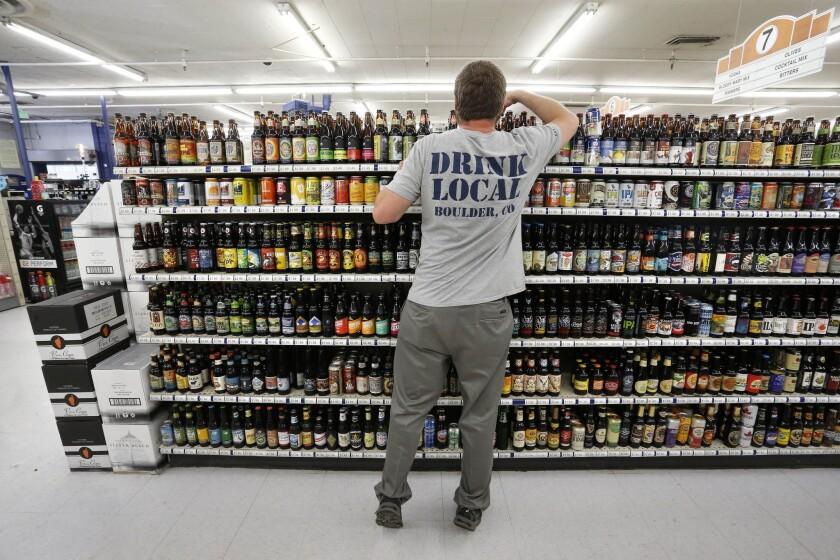 En imagen del 9 de junio de 2016, el encargado de la sección de cervezas, Kippie Loughlin, ordena una estantería con cientos de variedades de cervezas en Liquor Mart de Boulder, Colorado. El gobernador de Colorado, John Hickenlooper, firmó el viernes 11 de junio una ley que permitirá gradualmente a los supermercados y tiendas de abarrotes vender cerveza, licores y vinos de alto contenido de alcohol. (AP Foto/Brennan Linsley)