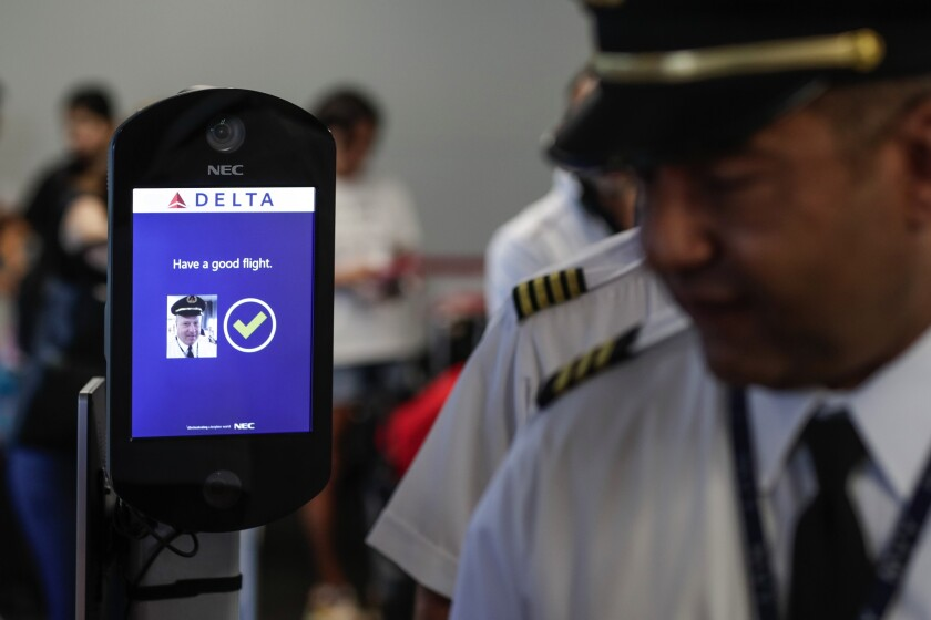 Airline crew members file past an airport biometric system.