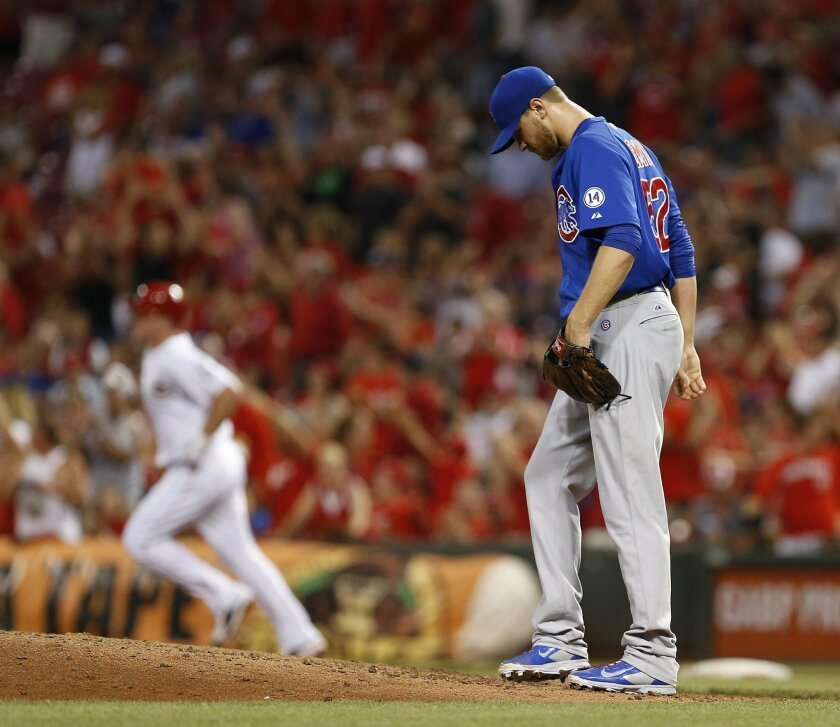Chicago Cubs relief pitcher Justin Grimm, right, kicks at the mound after giving up a two-run homer to Cincinnati Reds Jay Bruce (32) during the sixth the inning of a baseball game, Monday, July 20, 2015, in Cincinnati. (AP Photo/Gary Landers)