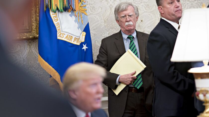 John Bolton, national security advisor, center, listens as President Trump comments on North Korea and China trade during a photo session Thursday in the Oval Office.