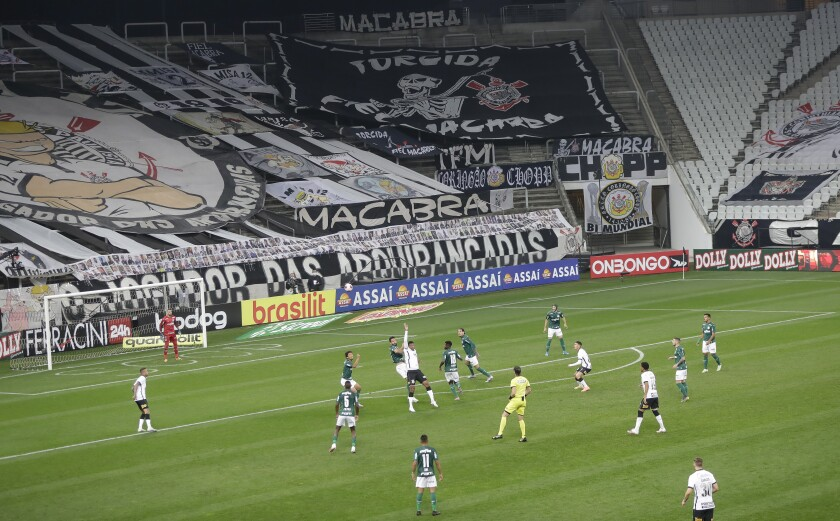 Players of Corinthians, in white, and Palmeiras play the Sao Paulo league first leg final soccer match at the Arena Corinthians stadium in Sao Paulo, Brazil, Wednesday, Aug. 5, 2020. The match is being played without spectators to curb the spread of COVID-19. (AP Photo/Andre Penner)