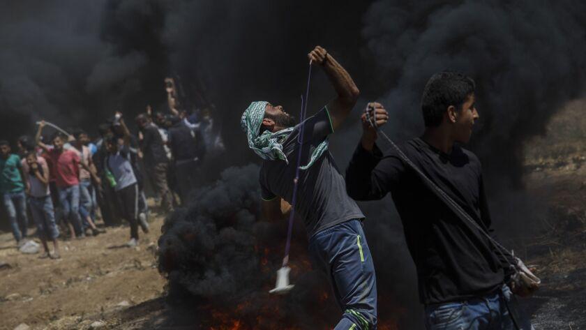 GAZA CITY, GAZA -- MONDAY, MAY 14, 2018: Protesters fling projectile at the border fence separating