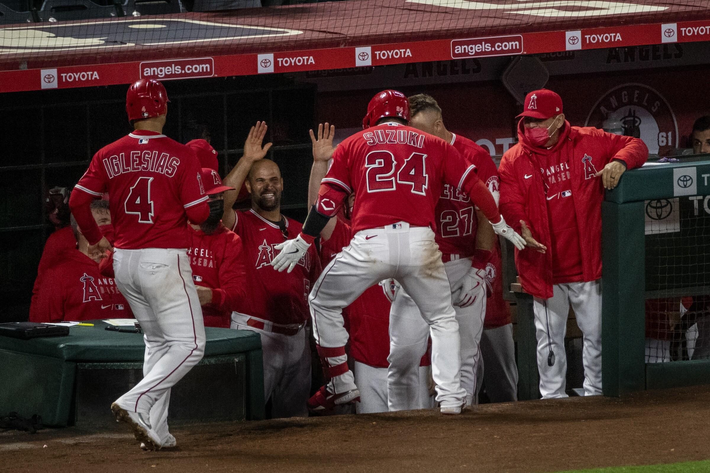 Angels catcher Kurt Suzuki is congratulated at the dugout after hitting a home run against the Texas Rangers.