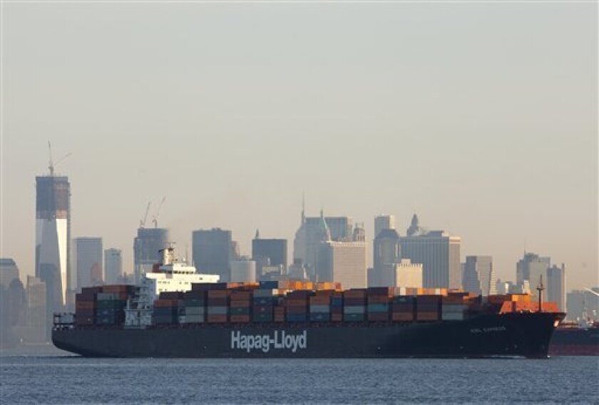In this photo of Feb. 4, 2012, a cargo ship, owned by German shipping company Hapag-Lloyd, crosses New York Harbor. The U.S. trade deficit widened in December, reflecting a jump in imports of autos and industrial machinery. For the year, the deficit climbed to the highest level since 2008 as both exports and imports rose to all-time highs. (AP Photo/Mark Lennihan)