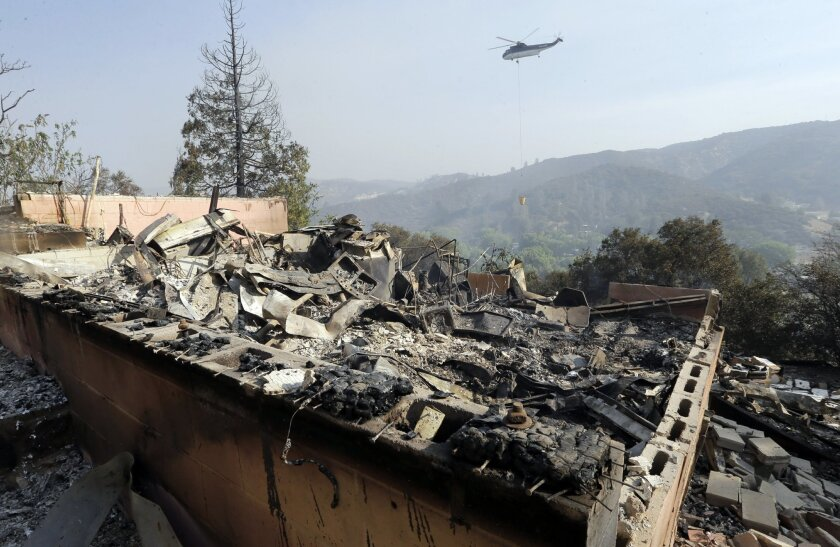 FILE- In this June 2, 2013, file photo, a firefighting helicopter carries a large water bucket behind a home that has been destroyed by a fire in Lake Hughes, Calif. The federal government sued a homeowner for nearly $25 million on Thursday, July 14, 2016, contending his negligence sparked a 2013 fire in the mountains east of Los Angeles that forced 5,000 people from their homes. (AP Photo/Reed Saxon, File)