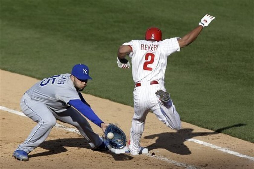 Philadelphia Phillies' Ben Revere, right, arrives at first base on a bunt as Kansas City Royals first baseman Eric Hosmer catches the throw in the fourth inning of a baseball game, Friday, April 5, 2013, in Philadelphia. Revere was called out on the play. (AP Photo/Matt Rourke)