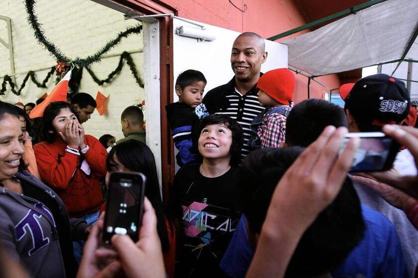 L.A. Clipper Caron Butler joins in the L.A. Boys and Girls Club holiday party. During the event, Bike Nation announced that it would begin rolling out its bike-share program in April.