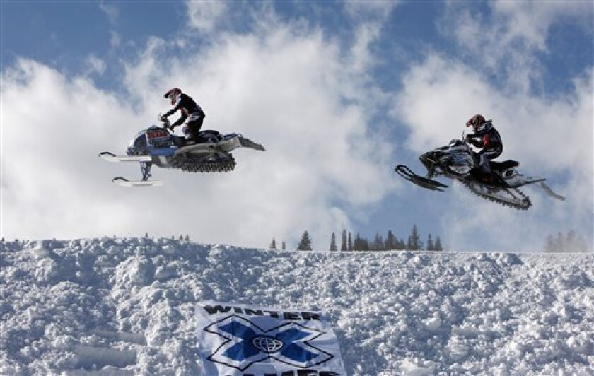FILE - In this Jan. 31, 2010, file photo, Colby Crapo, left, leads Carl Schubitzke over a jump during a heat to determine placement in the snowmobile snocross final at the Winter X Games at Buttermilk Mountain outside Aspen, Colo. After the death last month of a competitor in a snowmobile crash at the Winter X Games, regulators have signaled they'll take a new look at the permitting process for the Winter X Games, including the possibility that they'll get more involved in the ins and outs of the actual events, which are usually left to ESPN's discretion. (AP Photo/David Zalubowski, File)
