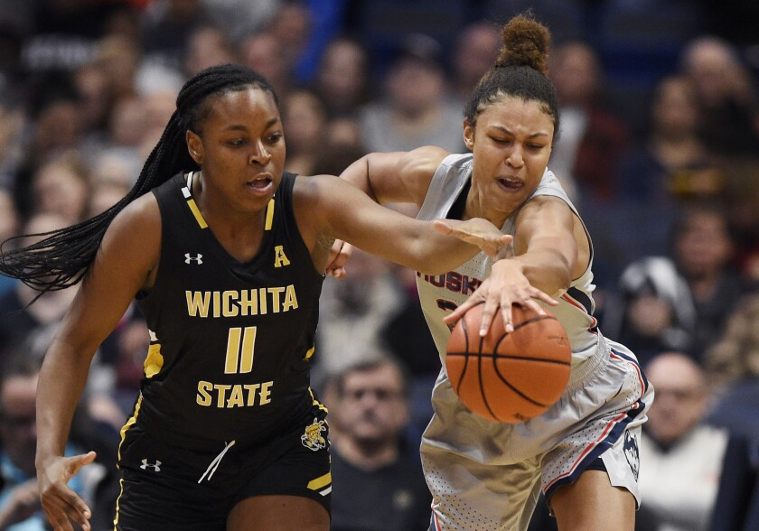 Wichita State's Ashlei Kirven, left, and Connecticut's Olivia Nelson-Ododa, right, reach for a loose ball during the first half of an NCAA college basketball game Thursday, Jan. 2, 2020, in Uncasville, Conn. (AP Photo/Jessica Hill)