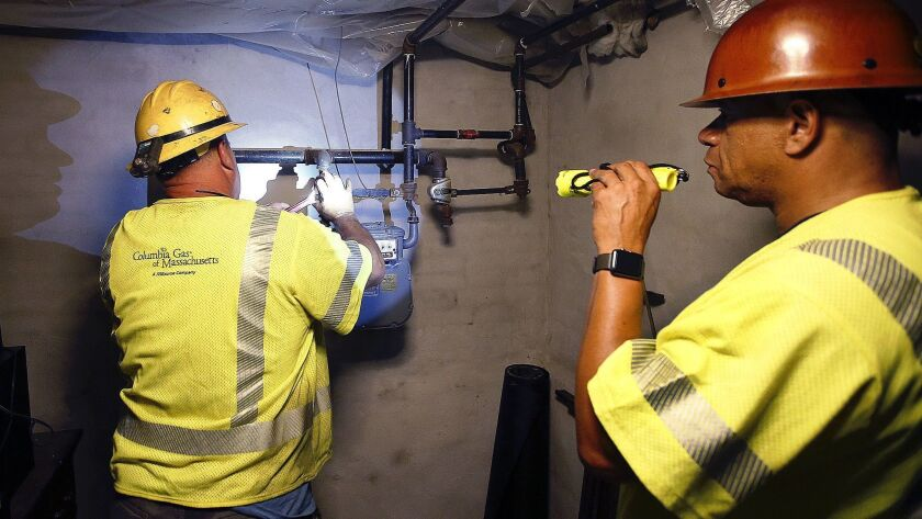 Columbia Gas employees shut off the gas in an Andover, Mass., home Friday. Multiple houses were damaged the day before from explosions triggered by a problem with a gas line that feeds homes in several communities north of Boston.