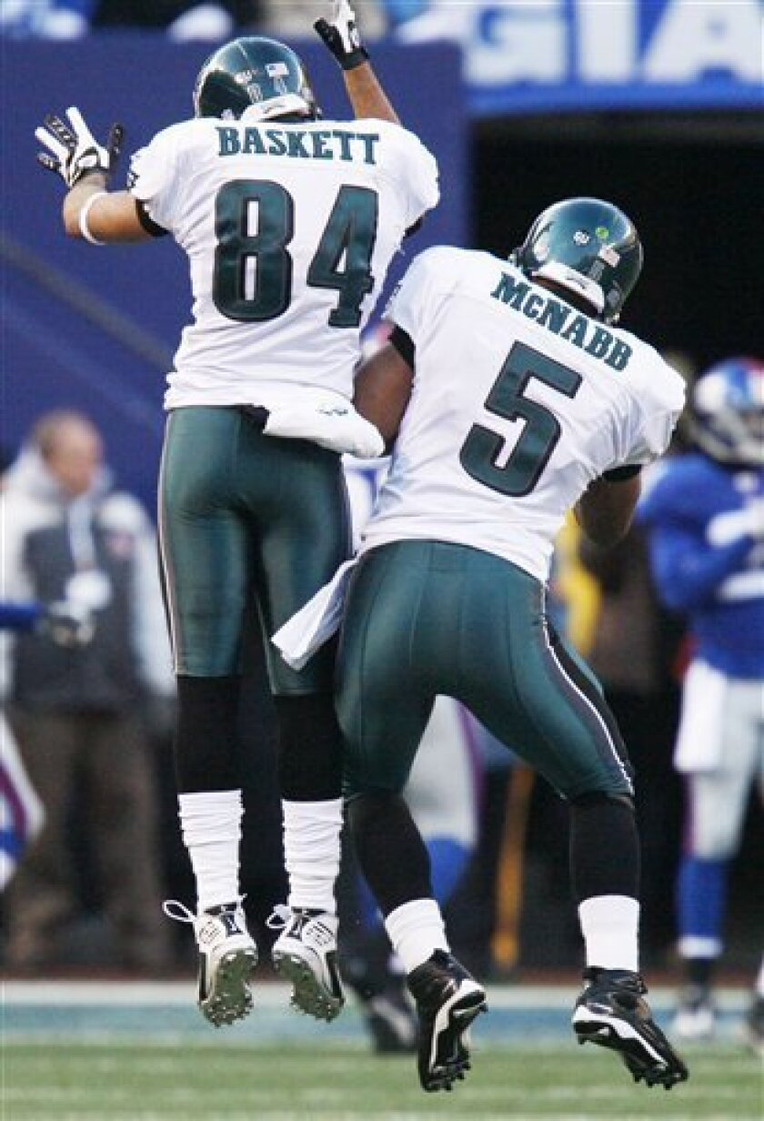 Philadelphia Eagles quarterback Donovan McNabb (5) and teammate Philadelphia Eagles wide receiver Hank Baskett (84) celebrate after the Eagles scored a touchdown during the fourth quarter of an NFL divisional playoff football game on Sunday, Jan. 11, 2009, at Giants Stadium in East Rutherford, N.J.