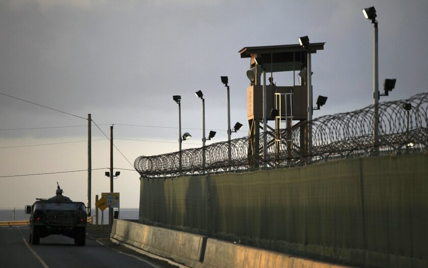 FILE – In this March 30, 2010, file photo, reviewed by the U.S. military, a U.S. trooper stands in the turret of a vehicle with a machine gun, left, as a guard looks out from a tower at the detention facility of Guantanamo Bay U.S. Naval Base in Cuba. (AP Photo/Brennan Linsley, File)