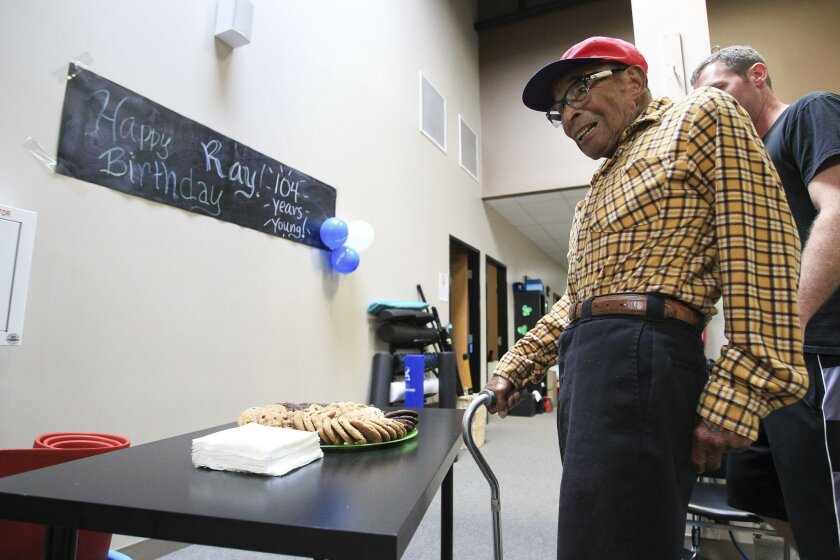 The nation's oldest Pearl Harbor survivor Ray Chavez, who will turn 104 on Thursday, is presented with cookies during a birthday party for him at the Personally Fit Gym in Rancho Bernardo on Tuesday.