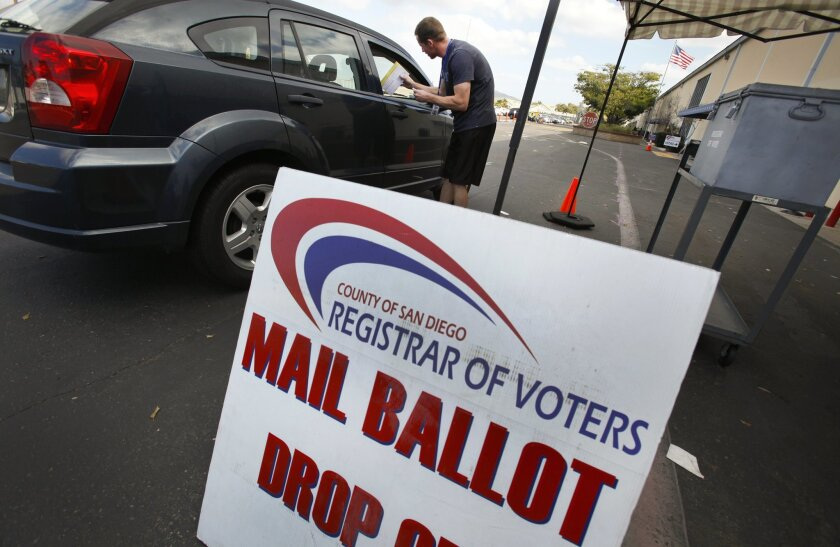Employee Derek Alschbach collects mail ballots from voters at a drop-off station in front of the county Registrar of Voters office a day before the special mayoral election.