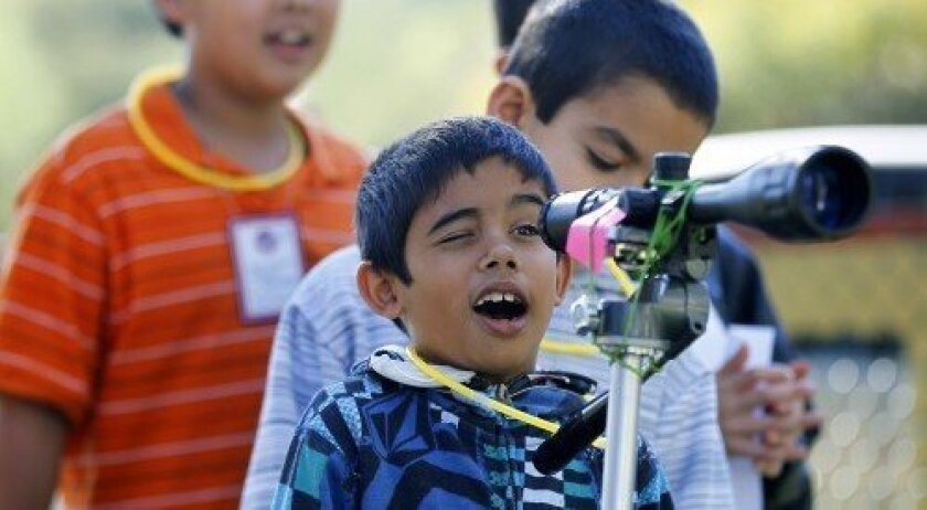 A student looks through the telescope on Science Discovery Day.