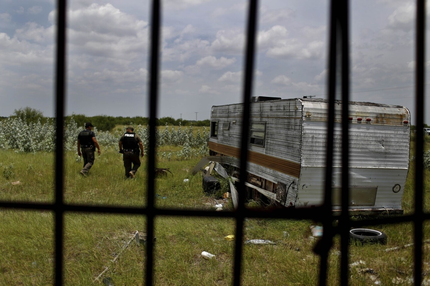 Deputies Domingo Aguirre, left, and Daniel Zamarripa, stand outside an abandoned trailer used by migrants for shelter on their journey north through Texas' Brooks County.