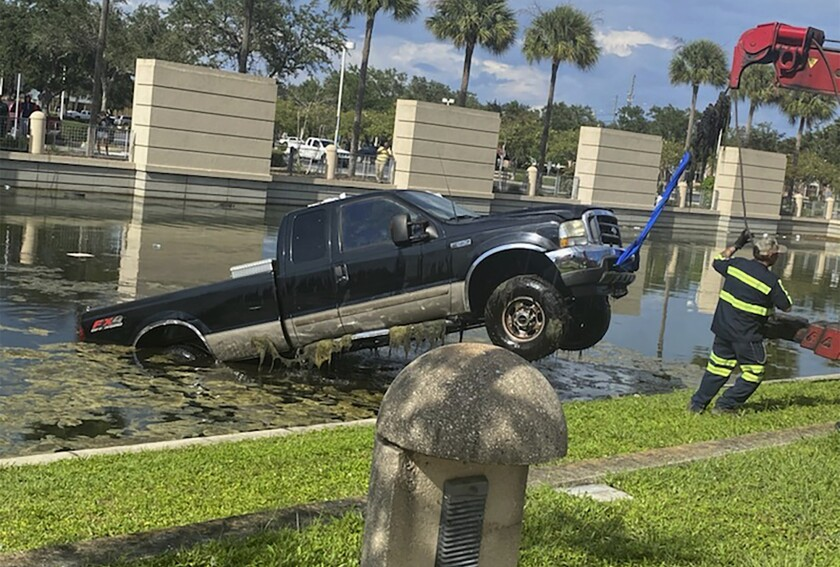 In this photo provided by the Florida Highway Patrol a vehicle is removed from a pond after it crashed outside the Pinellas County Justice Center, Wednesday, Sept. 2, 2020, in Clearwater, Fla. The 64-year-old driver was attempting to pull into a spot when his boot became entangled with the accelerator and vaulted into the retention pond, according to the Florida Highway Patrol. The truck became fully submerged, but deputies at the courthouse were able to help the man to safety. (Florida Highway Patrol via AP)