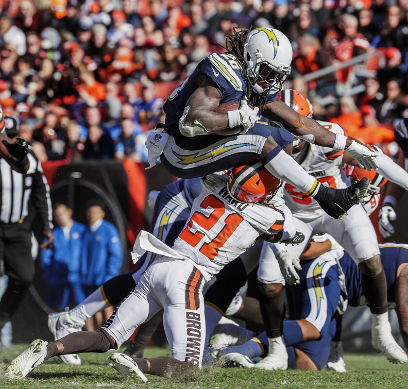 Chargers running back Melvin Gordon leaps over Cleveland Browns defensive back Denzel Ward on a second half run.