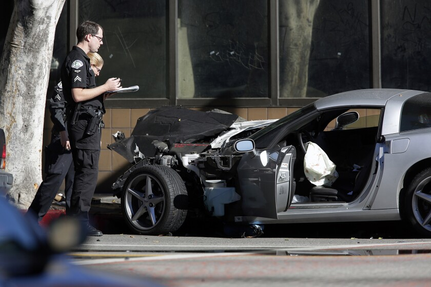 Police investigators at the scene where a silver Corvette crashed at the intersection of Olympic Blvd. and Los Angeles Street after a pursuit in December 2013. The driver of the Corvette died after an officer-involved shooting at the end of chase.