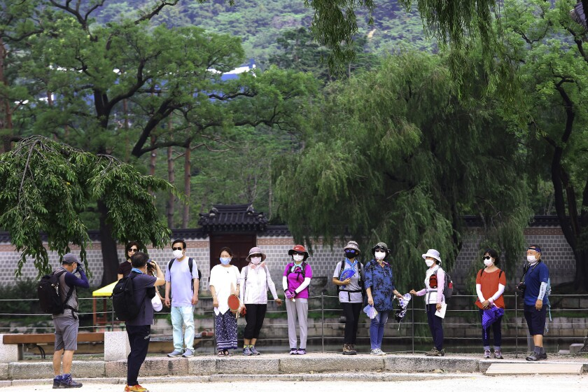 Visitors wearing face masks to help protect against the spread of the coronavirus pose to take pictures at the Gyeongbok Palace in Seoul, South Korea, Monday, Aug. 17, 2020. South Korea counted its fourth straight day of triple-digit increases in new coronavirus cases Monday as the government urged people to stay home and curb travel. (AP Photo/Ahn Young-joon)